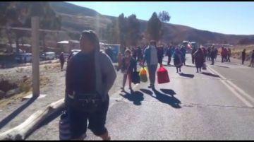 Pasajeros recorren a pie la carretera por el bloqueo en la vía Potosí- Sucre