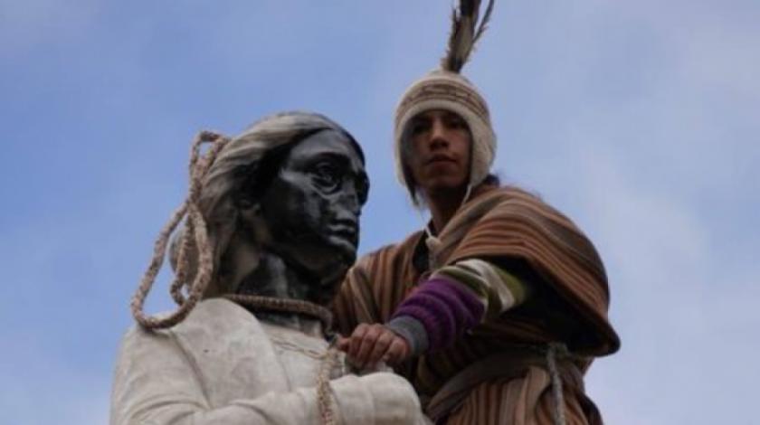 Un hombre de un grupo de manifestantes pinta e intenta tumbar el monumento de Cristóbal Colón