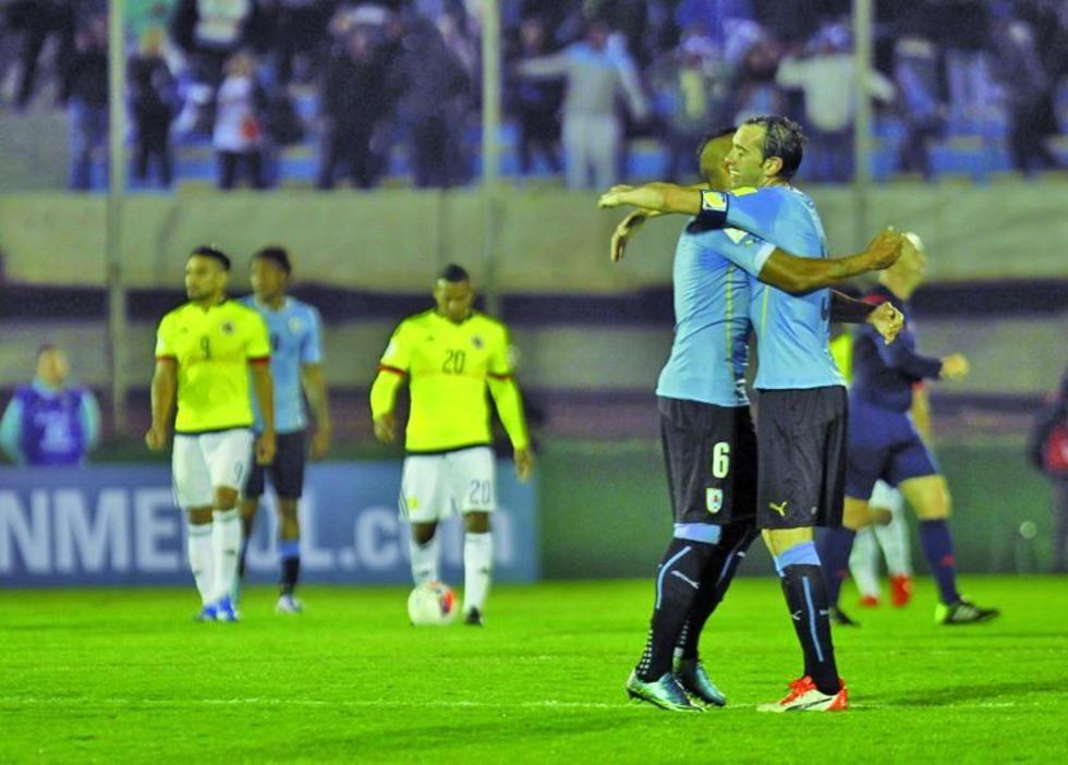 El jugador uruguayo Diego Godín (d) celebra su gol con su compañero Álvaro Pereira (c).