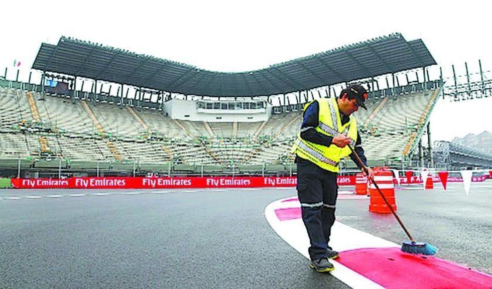 Un trabajador limpia la pista por la que corredores como Lewis Hamilton harán rugir sus motores.