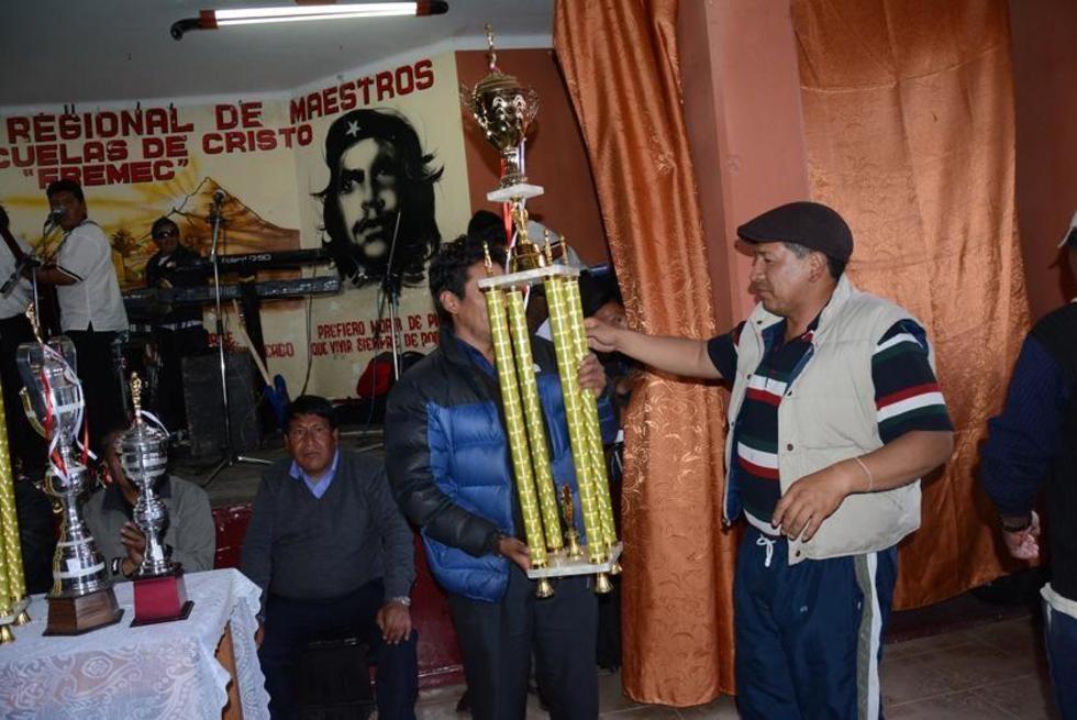 El representante de una de las federaciones recibe el trofeo de campeón.