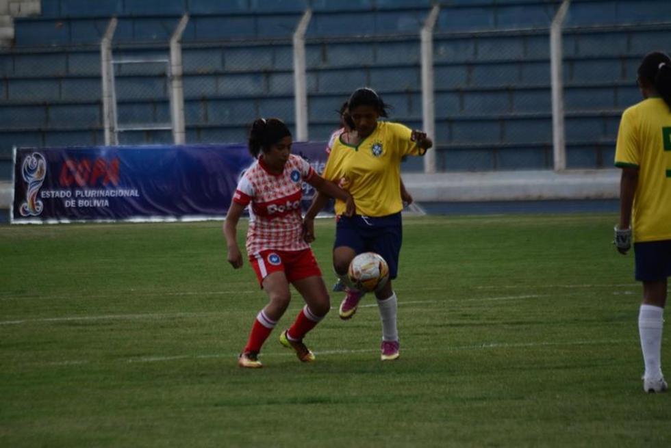 Las futbolistas de Potosí (d) intenta quitar el esférico.