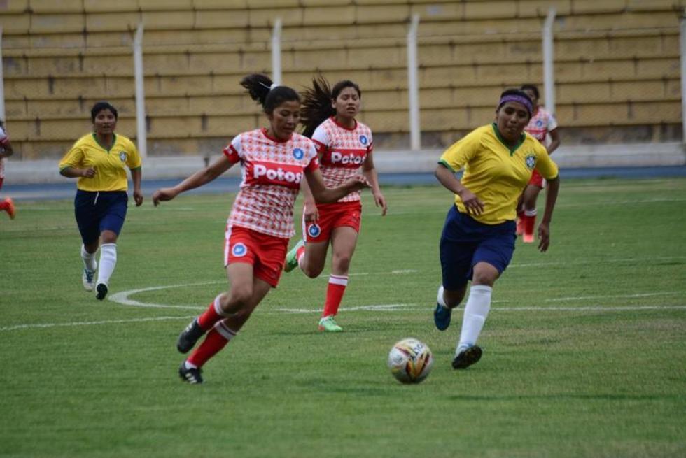 Las futbolistas se disputan el balón.