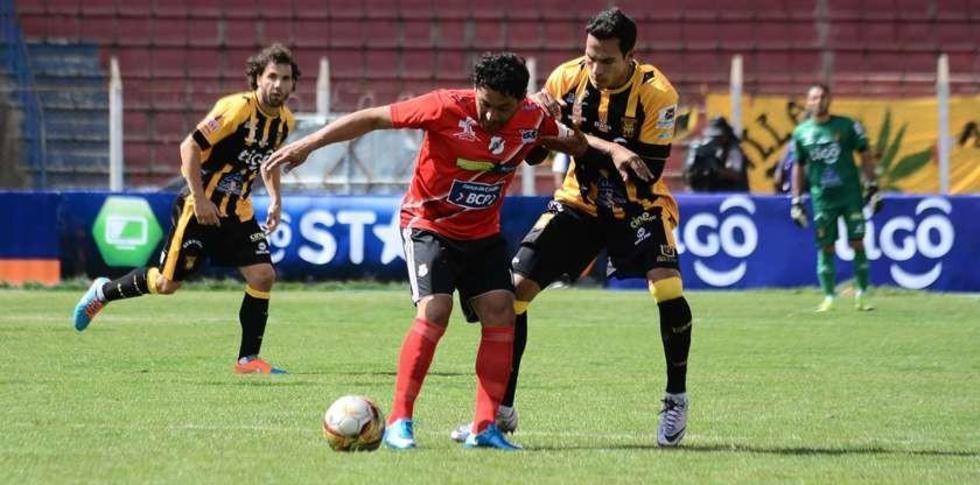 Darwin Peña soporta la marca del zaguero Luis Maldonado.