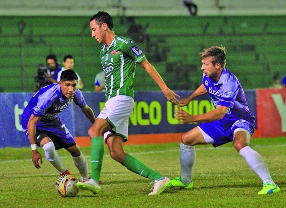 Carlos Saucedo (c) esquiva la marca de Rodrigo Ávila (i) y Claudio Centurión (d).
