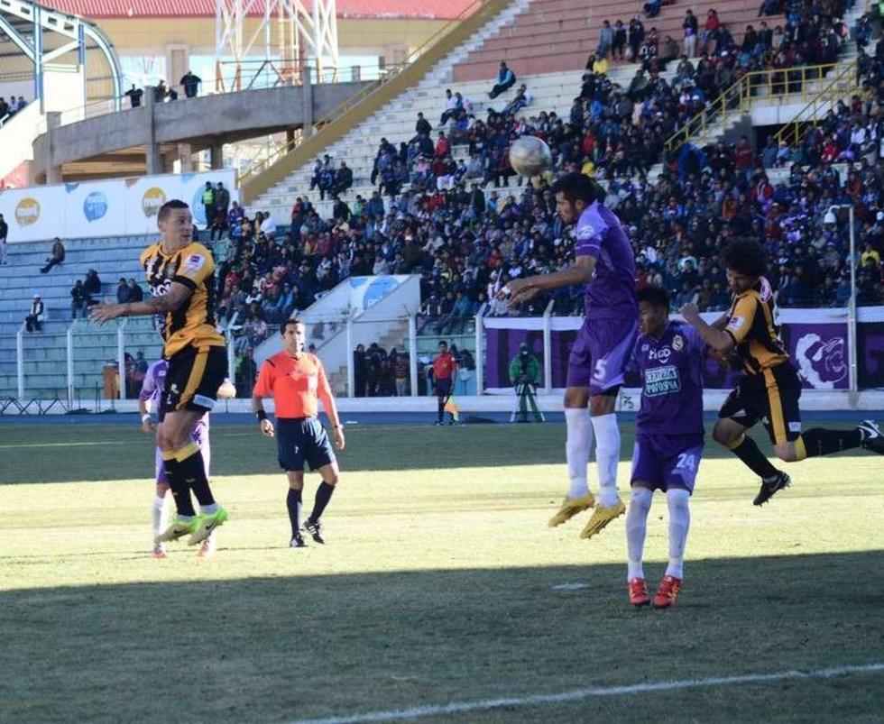 El zaguero Pablo Pedraza despeja el balón (c).