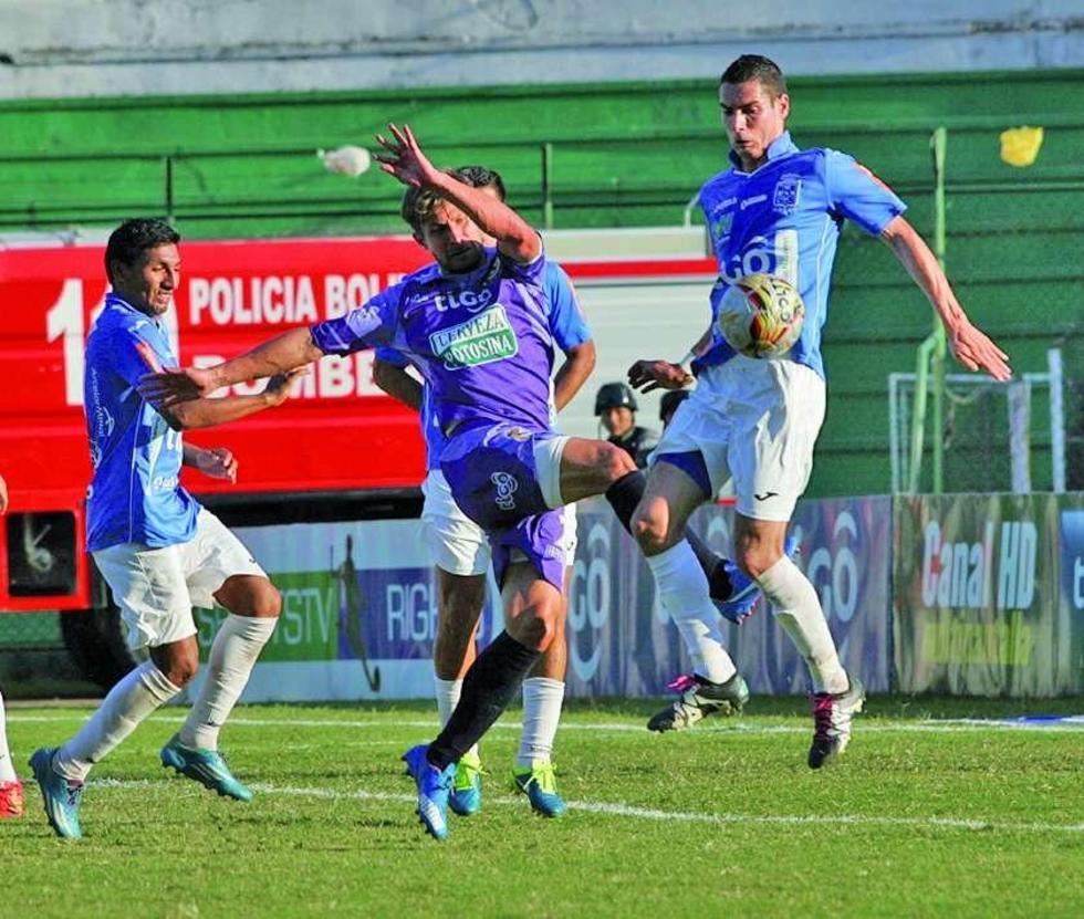 Claudio Centurión (c) disputa el balón en medio de tres rivales.