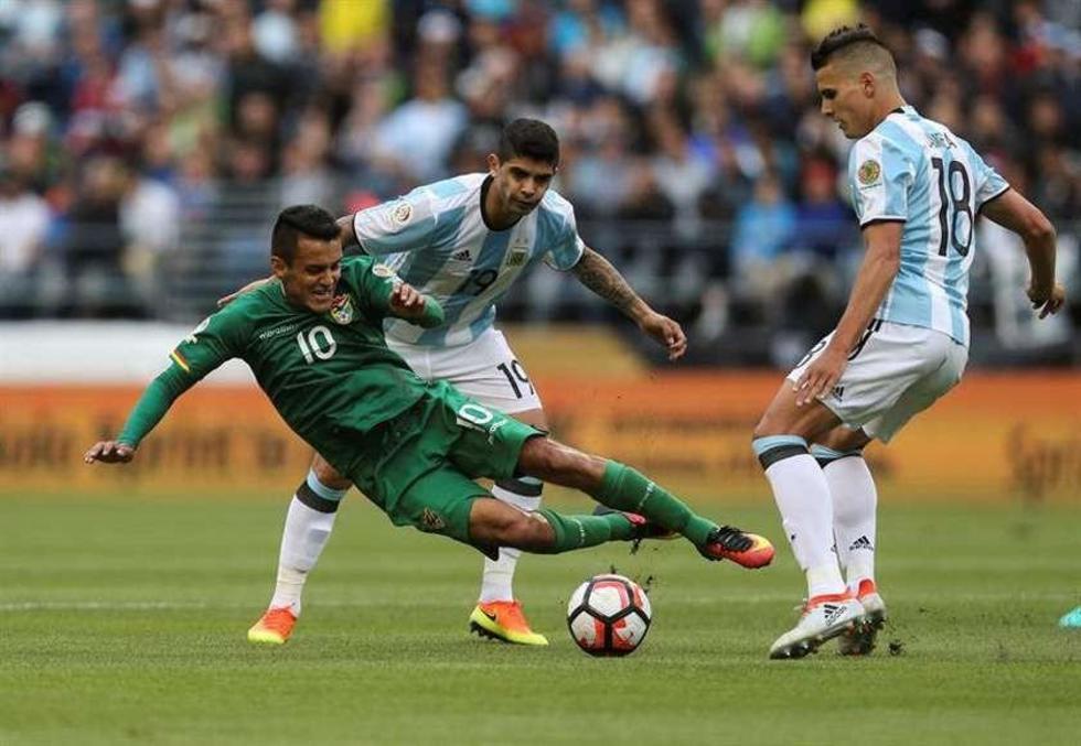 Jhasmani Campos (i) cae ante la marca de los argentinos Ever Banega (atrás) y Erik Lamela (d).
