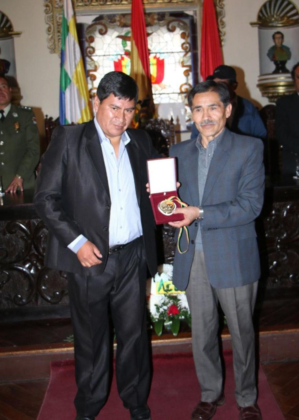 El gobernador Cejas entrega la medalla a Félix Muruchi.