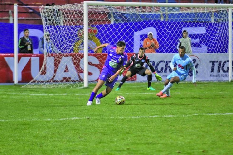 Carlos Saucedo trata de quitarse la marca de Edemir Rodriguiez y el meta Diego Zamora.