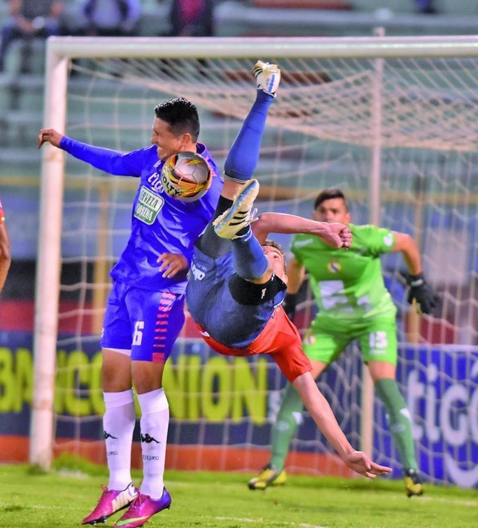 Limbert Méndez (i) despeja el balón ante la arremetida de su rival.