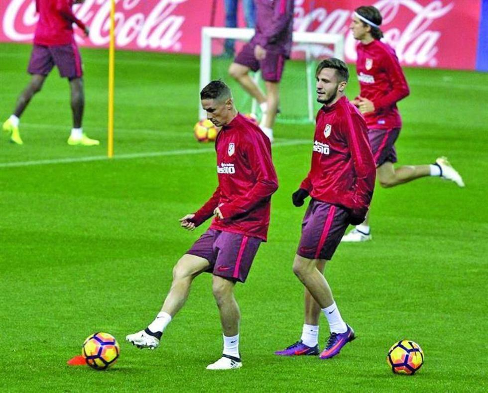 El delantero de Atlético, Fernando Torres, controla el balón.