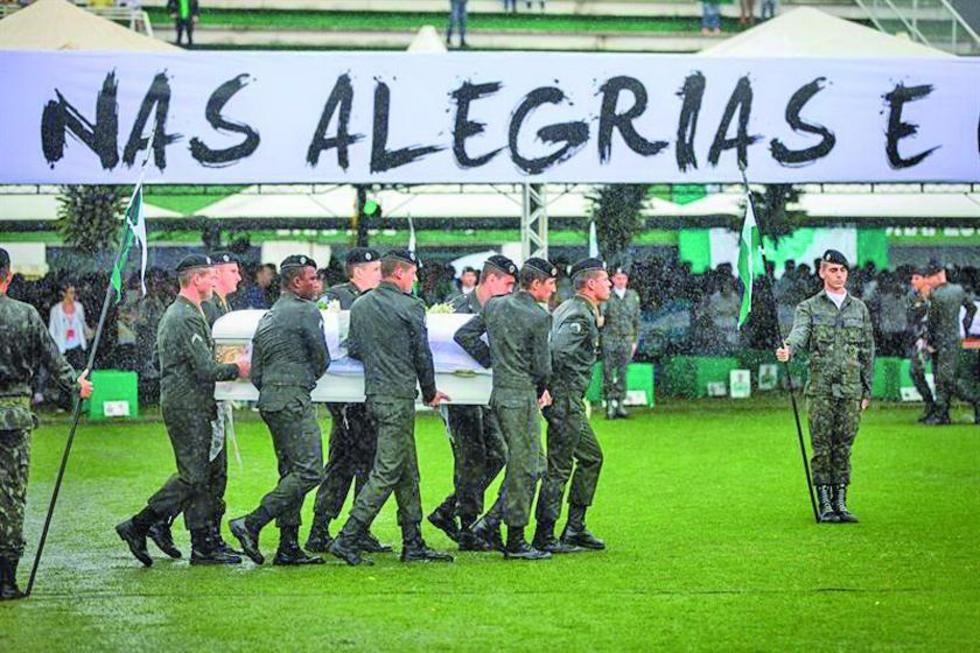Militares brasileños cargan los féretros de los jugadores y equipo técnico del club brasileño Chapecoense durante el vel