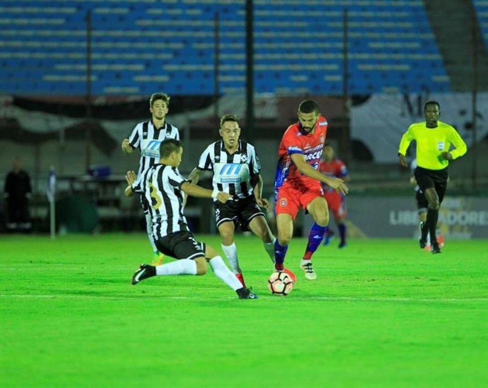 El jugador del Universitario de Sucre, Alejandro Quintana, disputa el balón con Emiliano Díaz (i), de Wanderers.