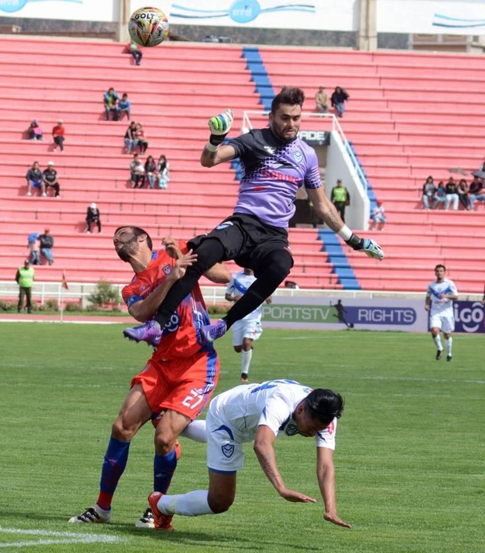 El meta Carlos Franco es derribado por su rival.