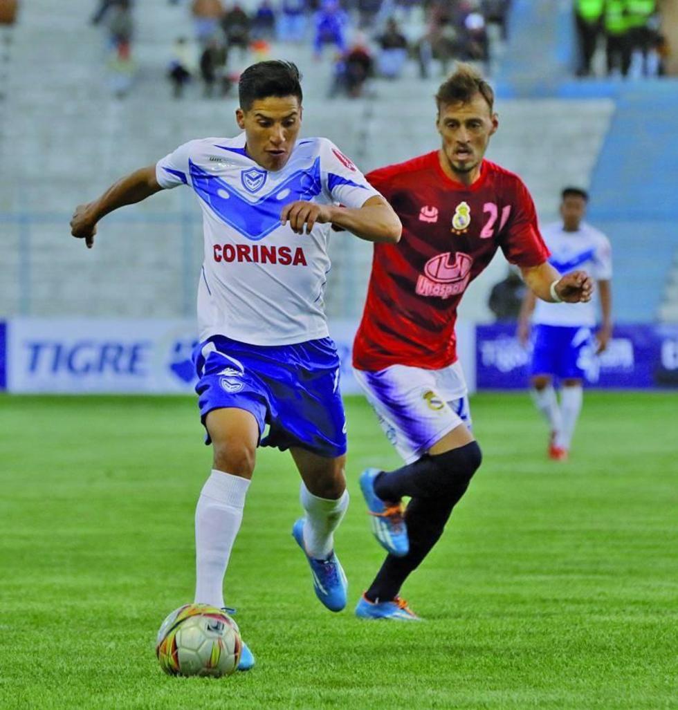 Ariel Juárez se lleva el balón ante la marcación de Víctor Galain.