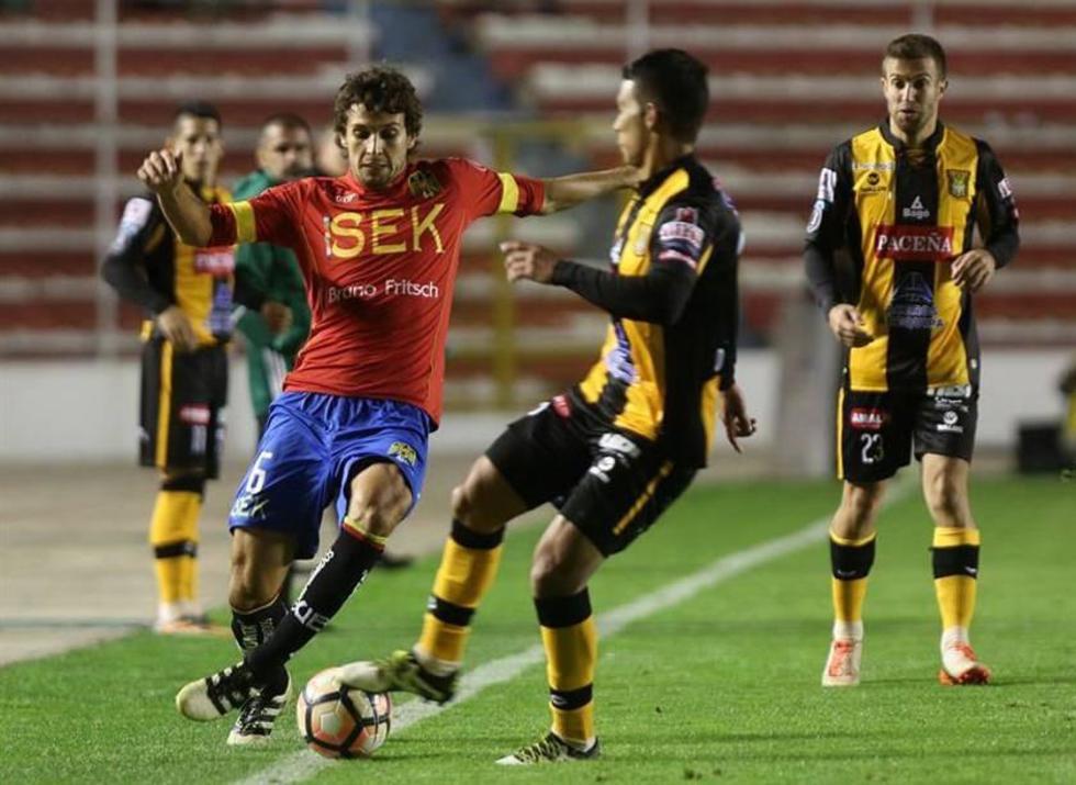 Lucas Domínguez (i) disputa un balón con Diego Bejarano (c) de The Strongest.