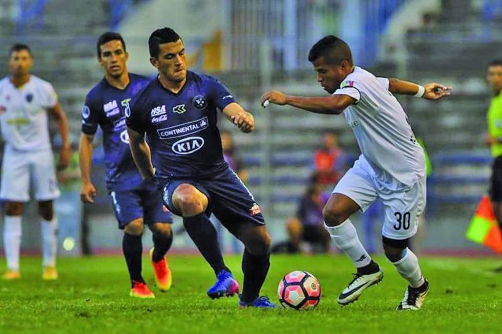Michael Márquez (d) de Estudiantes de Caracas controla la pelota.
