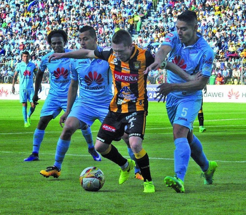 Alejandro Chumacero busca eludir la marca de sus rivales.