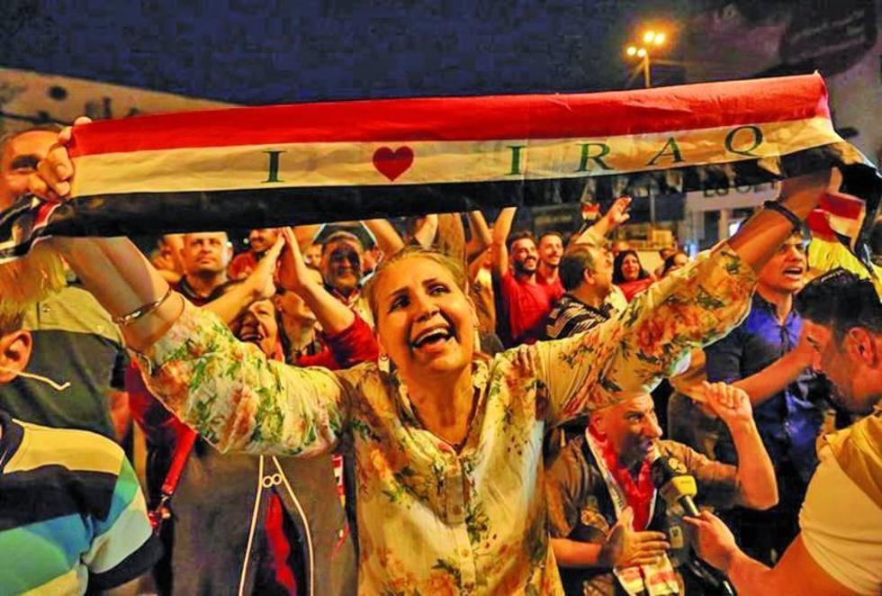 """Varios ciudadanos iraquíes celebraron en las calles. Una mujer sostiene la bandera de su país con el lema """"yo amo Irak""""."""