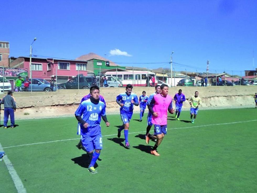 Los futbolistas trotan alrededor de la cancha.