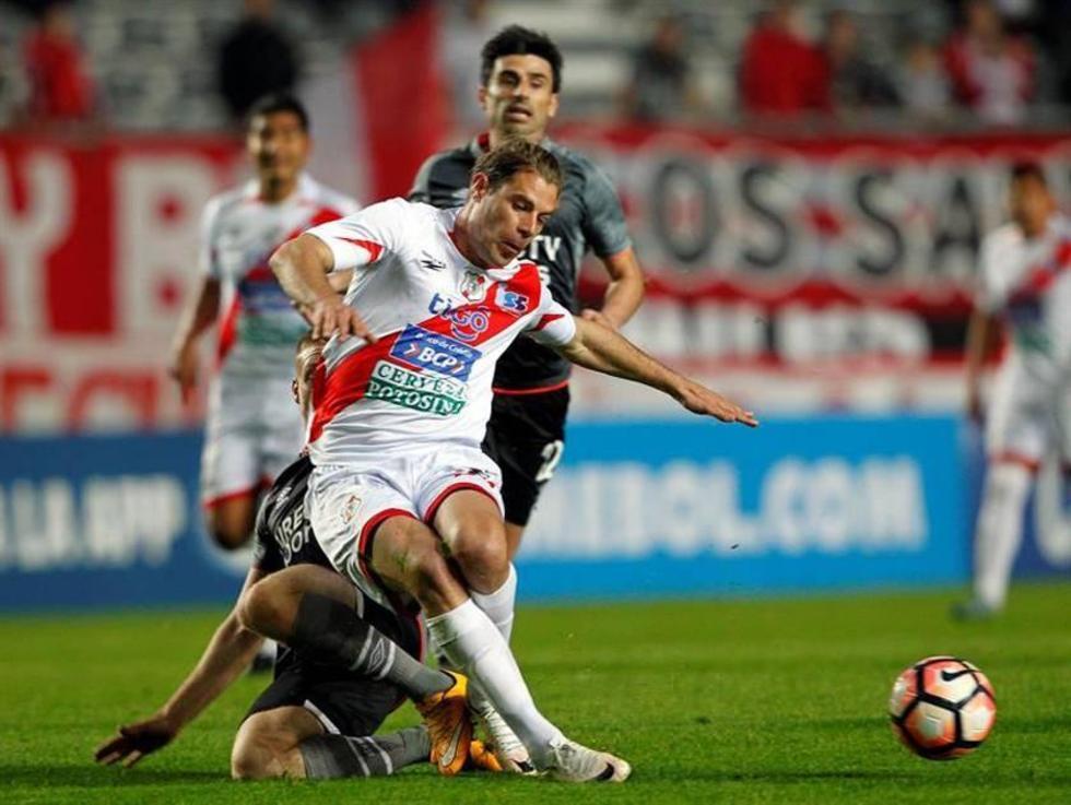 Santiago Ascacibar, de Estudiantes, comete una falta a Cristian Alessandrini, de la banda roja.