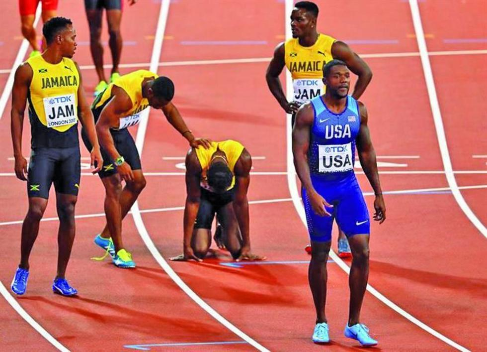 El jamaicano Usain Bolt es ayudado por sus compañeros.
