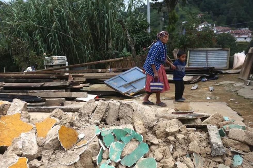Una anciana camina junto a su nieto por los escombros de su casa.