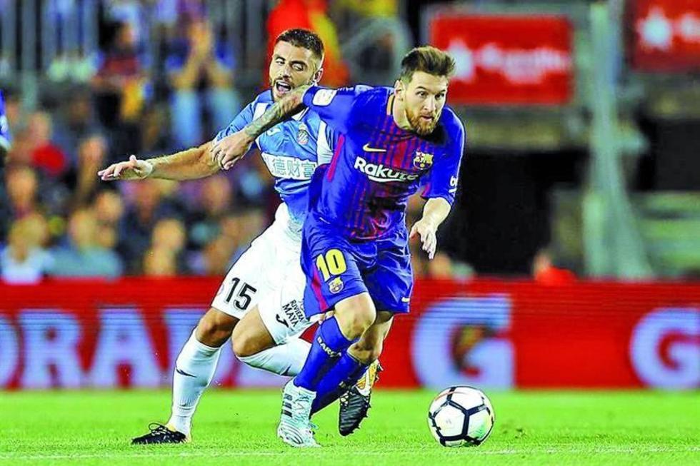 Leo Messi controla el balón ante la marca de su rivale.