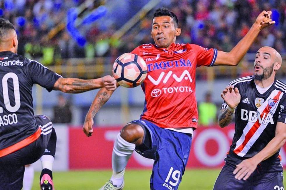 Gilbert Álvarez (c) disputa un balón con sus rivales.