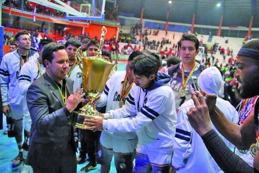 El DT Giovanny Vargas sostiene el trofeo junto a su equipo.