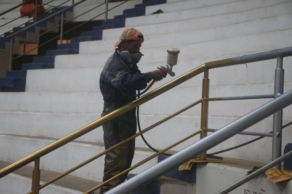 Trabajadores pintan las barandas.