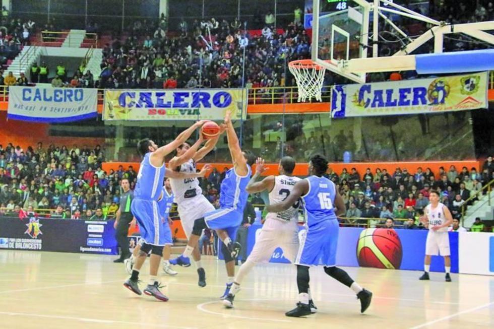 Cristian Camargo es bloqueado por dos rivales.