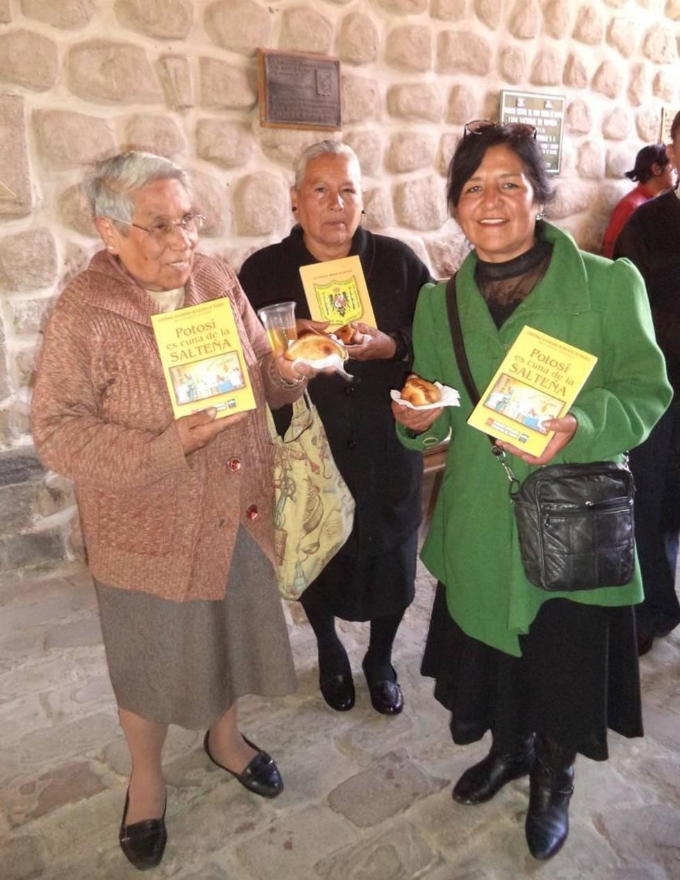 La población muestra el libro, la salteña y un refresco popular.