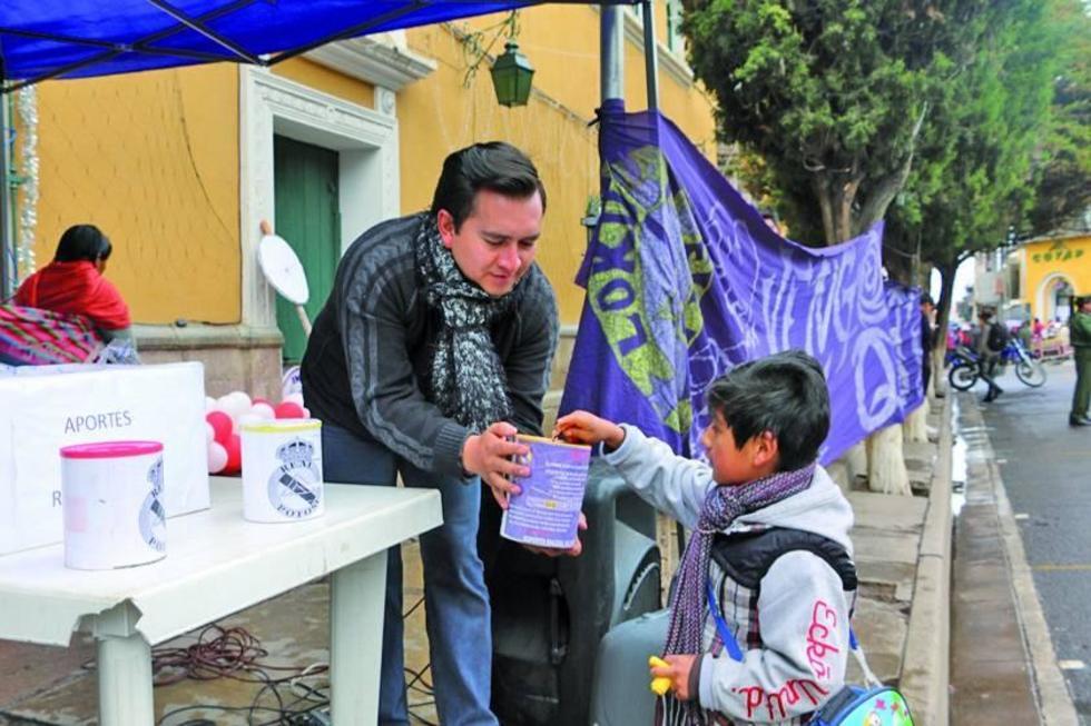 Un niño hace su aporte voluntario para salvar al plantel lila.