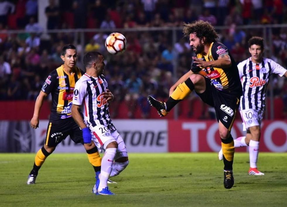 Fernando Marteli (d) trata de despejar un balón.