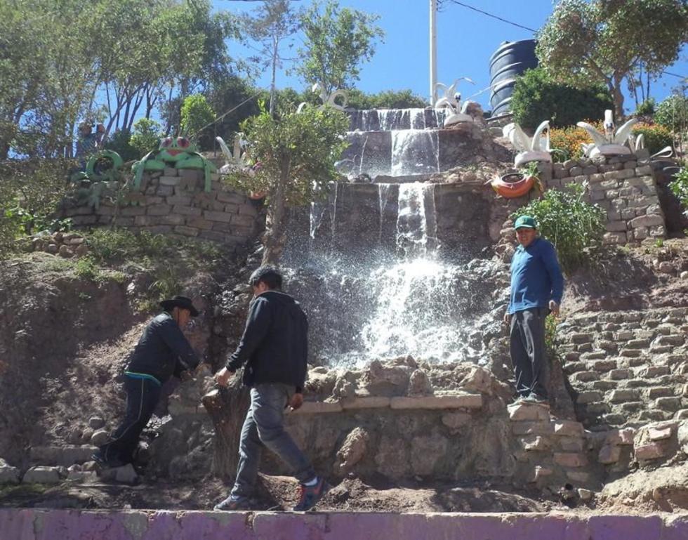 El alcalde (izq.) supervisa la caída del agua en una fuente.