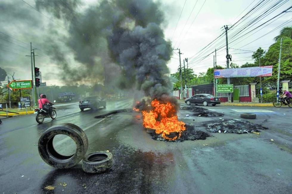 Manifestantes levantan una barricada en protesta contra el alza del combustible.