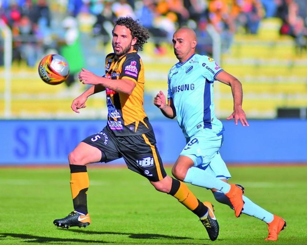 Fernando Marteli cubre el balón ante la arremetida de Marcos Riquelme.
