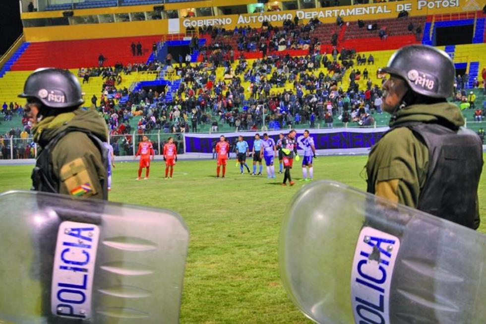 Policías forman un cordón de seguridad para evitar que jugadores entren a la cancha al final del cotejo.