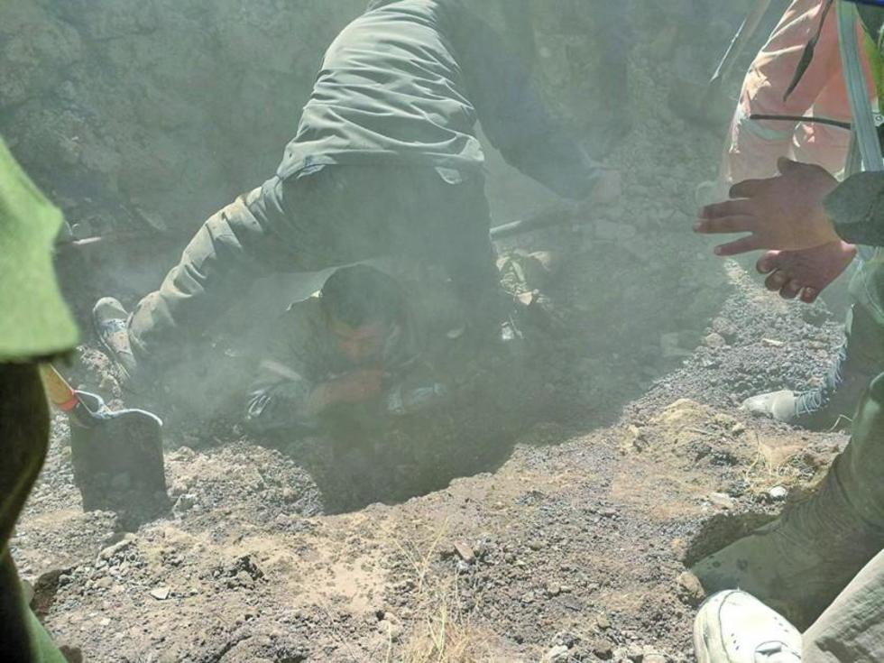 Un efectivo remueve los escombros con una pala para sacar a Jhonny Calle.