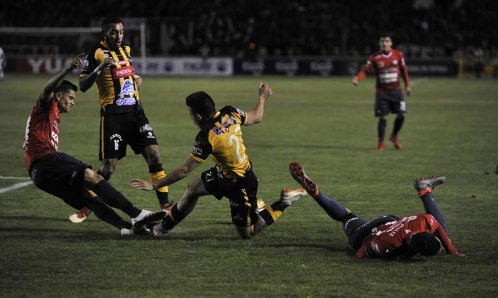 Henry Vaca (d) disputa el balón con su rival.