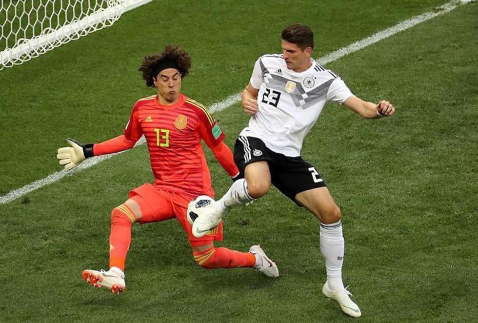 El portero de México, Guillermo Ochoa, ataja el balón a Mario Gomez.