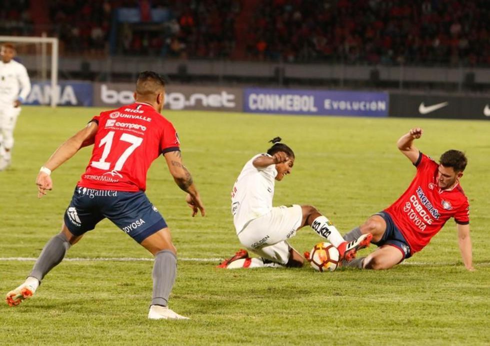 Edison Preciado (c) del Deportivo Cuenca, disputa e balón con Fernando Saucedo, de Wilstermann.