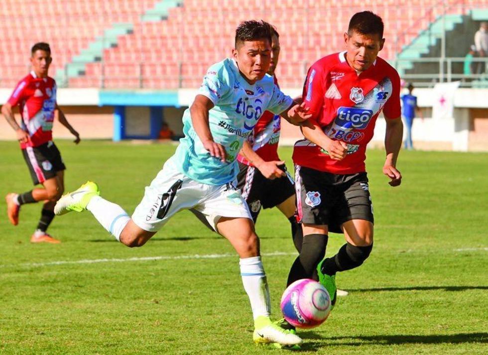 Luis Torrico, de Nacional, intenta que su rival pueda rematar.