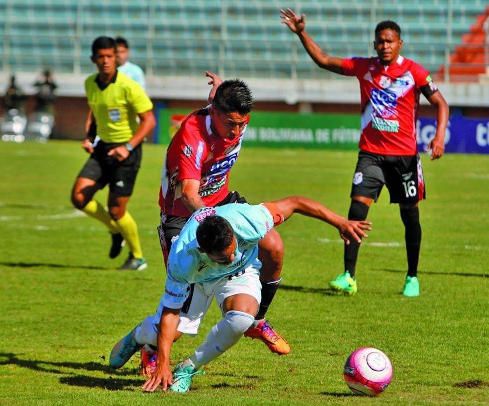 Charles da Silva, de Aurora, protege el balón.