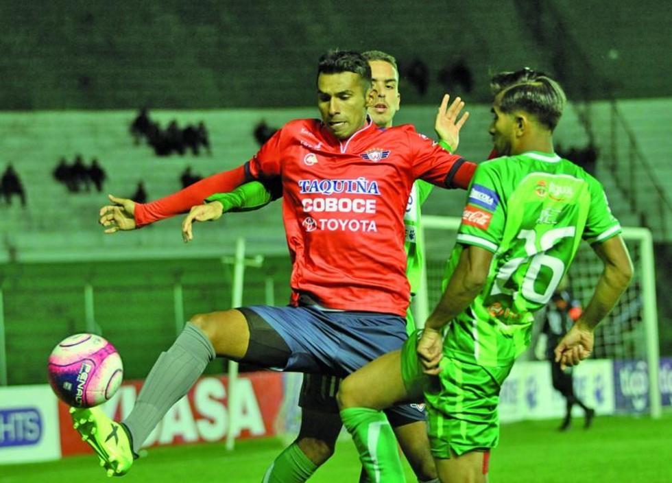 Gilbert Álvarez es cercado por dos jugadores del cuadro local.