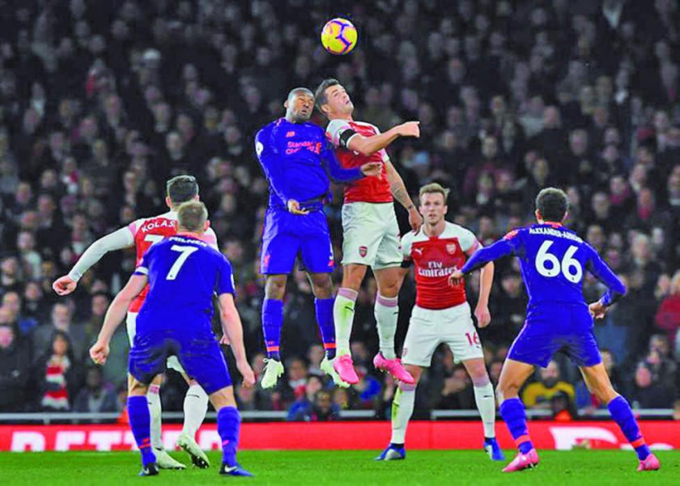 Georginio Wijanldum,de Liverpool, y Granit ÊXhaka, de Arsenal, se disputan el balón.