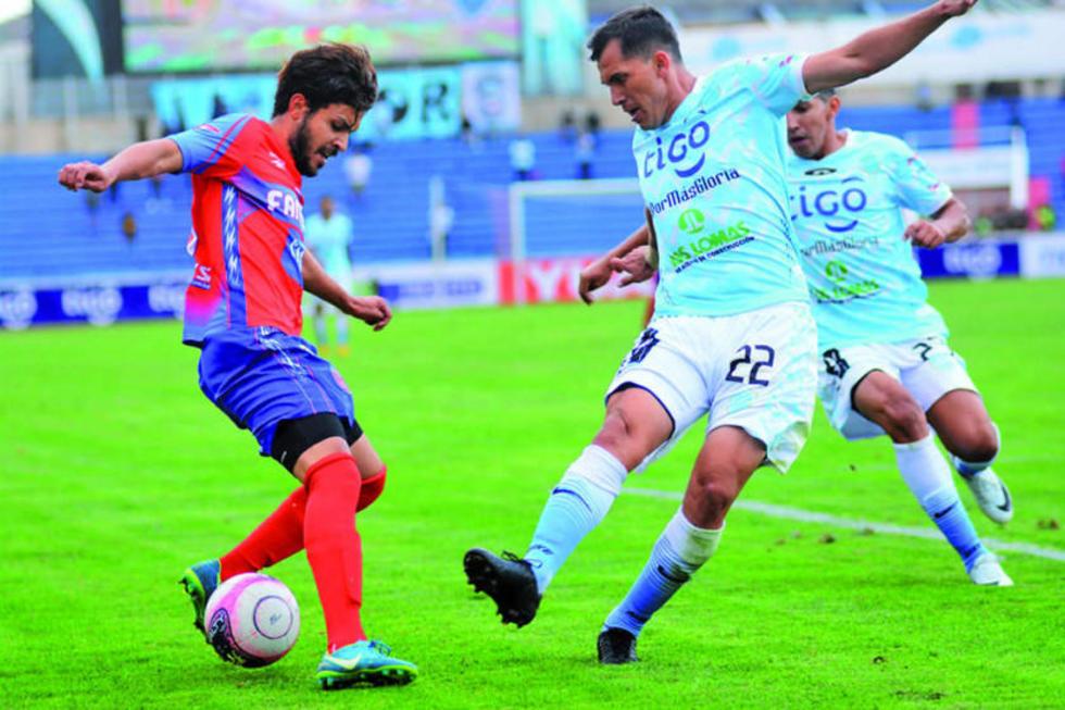 El defensa de Aurora Luis Barbosa (d) trata de detener a su rival.