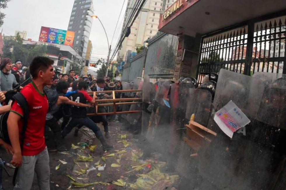 Miembros de las plataformas del 21F se enfrentan con policías a las puertas del edificio del Tribunal Supremo Electoral.